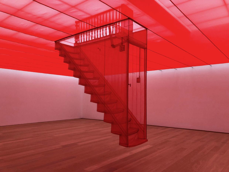 Das Bild stellt eine rote Treppe mit 13 Stufen aus halbdurchsichtigem Stoff dar, welche ein Stück über dem Boden des Ausstellungsraums schwebt.