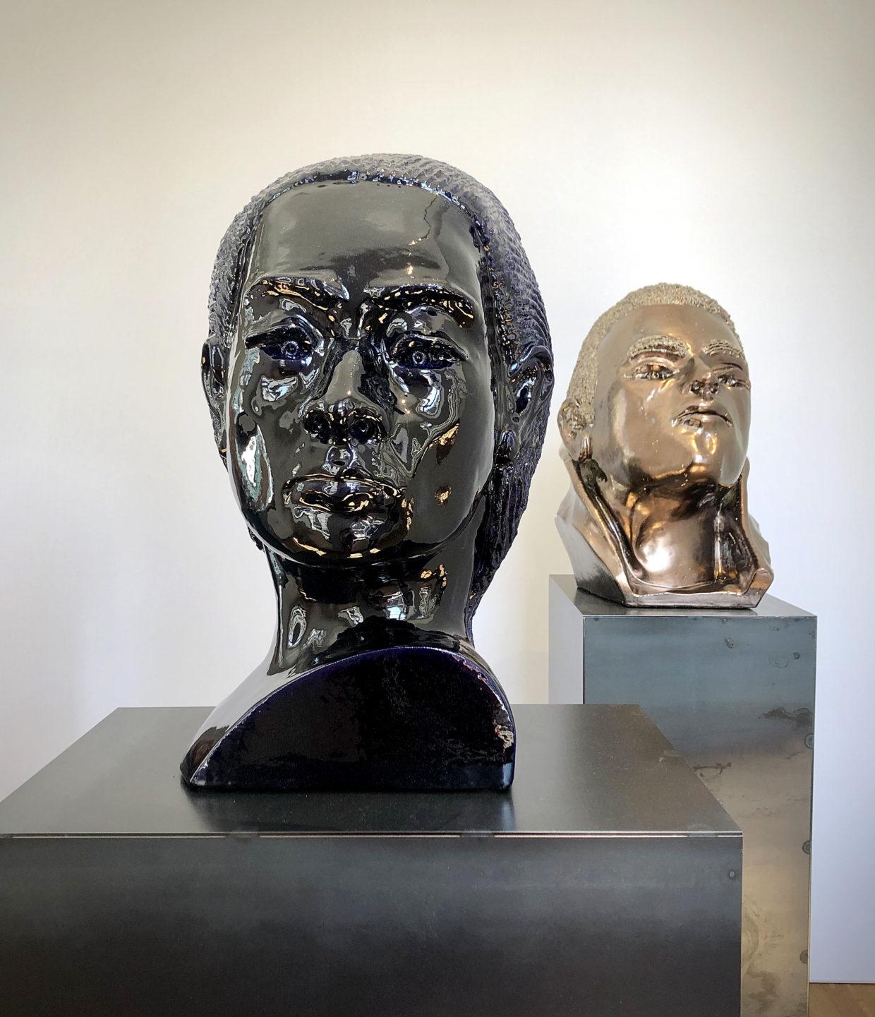 Dieses Bild zeigt eine dunkelblau schimmernde Frauenbüste aus Keramik und einen vollplastischen Männerkopf in goldener Farbe.